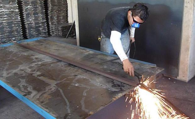 Using a plasma cutter to cut the steel for the planchas.