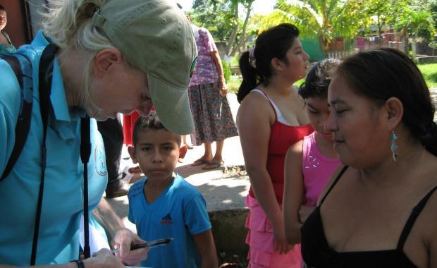 Dee recopilando información de una mujer en La Barca, que asiste a una reunión de la comunidad.