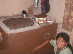 La beneficiaria pinta su estufa con tierra de color, mientras tuesta cafe al mismo tiempo.