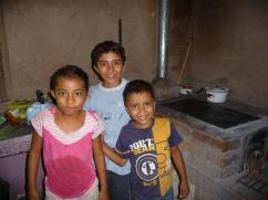 Estos tres niños están felices con su nueva estufa 2x3 de ladrillo.