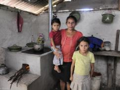 A mom and her family in her home with a dirt floor.