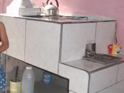 Observe la leña extinguida que es guardada para más tarde en un recipiente para cenizas, debajo de la estufa.