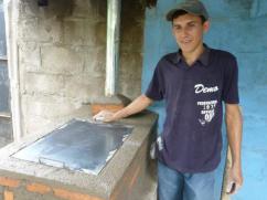 Un técnico y la estufa que acaba de construir.