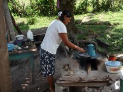 Ella esta cocinando en una cocina de típico estilo hondureño, mientras espera a que su nueva estufa 2x3 se seque.