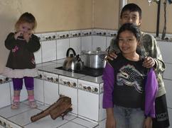 Niños en la cocina al lado del fuego.