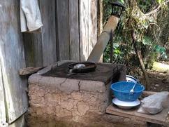 Estufa vieja de lodo con chimenea inclinada y cerca a la cocinera