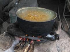 Hervir maize en una olla negra.