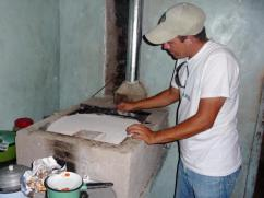 Don Walter está utilizando el Cinco para remover el nivel de ceniza que sirve para asegurar que la plancha se caliente correctamente.